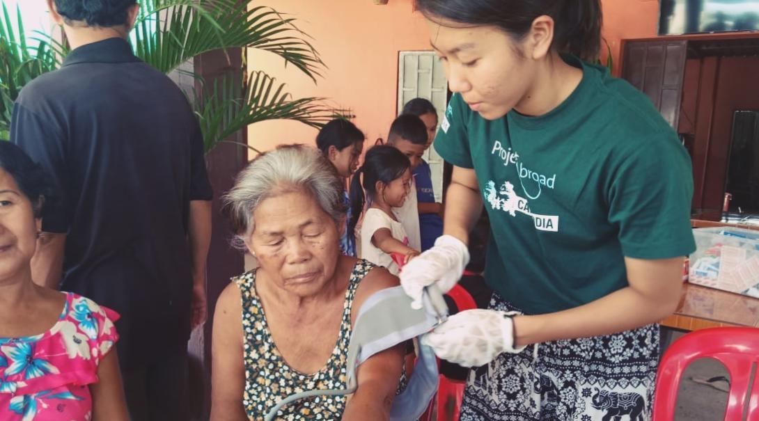 日本人高校生の公衆衛生ボランティアがカンボジアの地域住民の血圧測定にあたる